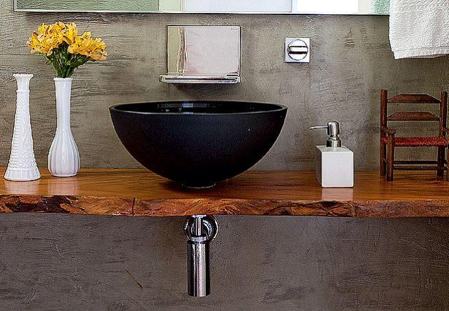 Bem servido de materiais ecologicamente corretos, este lavabo recebeu revestimento de cimento queimado cinza
