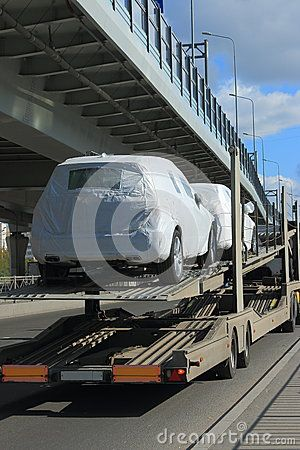 Two cars in a white shipping carton on the upper deck of the trailer