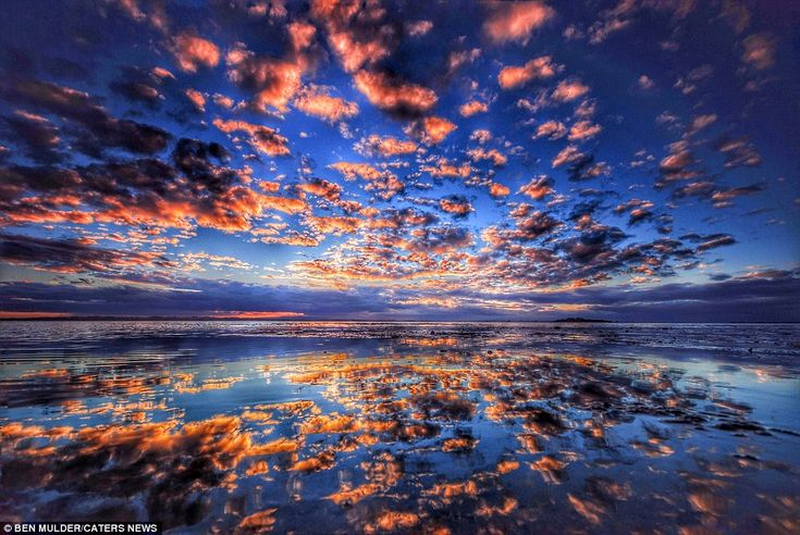 The stunning images show the vivid colours of the sunset reflected in the shallow see wate...