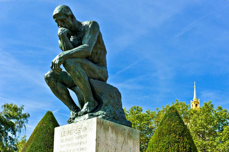 The Thinker sculpture by August Rodin in the Rodin Museum garden, Paris