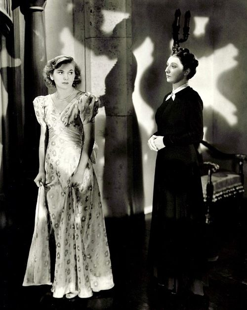 "Joan Fontaine and Judith Anderson in publicity still for Rebecca (1940, dir. Alfred Hitchcock) (via)  ""Her voice dropped to a whisper. 'Sometimes, when I walk along the corridor here, I fancy I hear her just behind me. That quick, light footstep. I could not mistake it anywhere. It's almost as though I catch the sound of her dress sweeping the stairs as she comes down to dinner.'   She paused. She went on looking at me, watching my eyes. 'Do you think she can see us,"