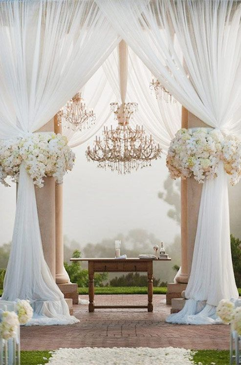 Golden chandeliers make this ceremony space the epitome of elegance. Outdoor wedding ceremony decor ideas