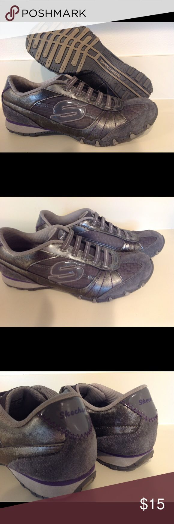 Sketchers Grey and silver with elastic straps 8.5 This is a pair of ladies Skechers Grey and silver and a purple trim, tennis shoes size 8.5 in very nice pre owned condition.  They are a leather and synthetic material. Only worn a few times.  See photos for more condition details.  Thank you for looking. Skechers Shoes Sneakers