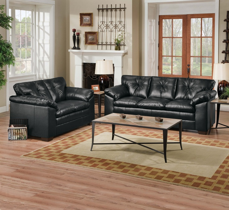 beautiful rich black leather sofa and love seat paired with a glass coffee table