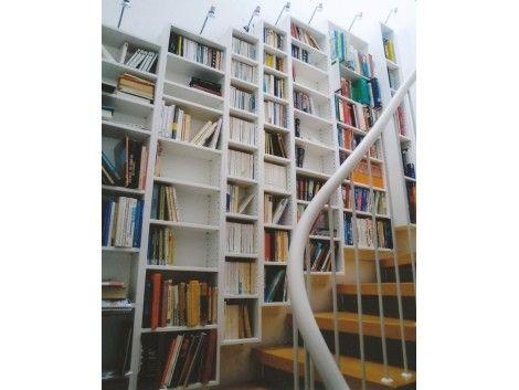 Bücherregal an der Treppe mit unterschiedlich großen Fächern