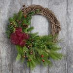 """Holiday Greens Grapevine Wreath - $99   Red Twig Dogwood and grapevine are artfully entwined to form a subtly distinctive base for this charming holiday wreath. Handmade using organically grown products, this holiday accent is decorated with sprigs of fragrant Noble Fir, mountain berry twigs, and clusters of faux berries then finished with a wired bow patterned in a berry print. The wreath will last longest in a location that's dry and cool (below 65°F).  20"""" diameter Indoor or outdoor use"""