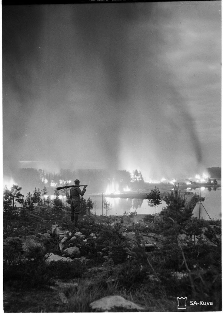 Finnish soldier looks at a burning town, 1944