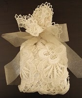 Gift bag, made from vintage lace doily and tied with gold shimmer organza ribbon. [September 2012: the source site apparently no longer exists].