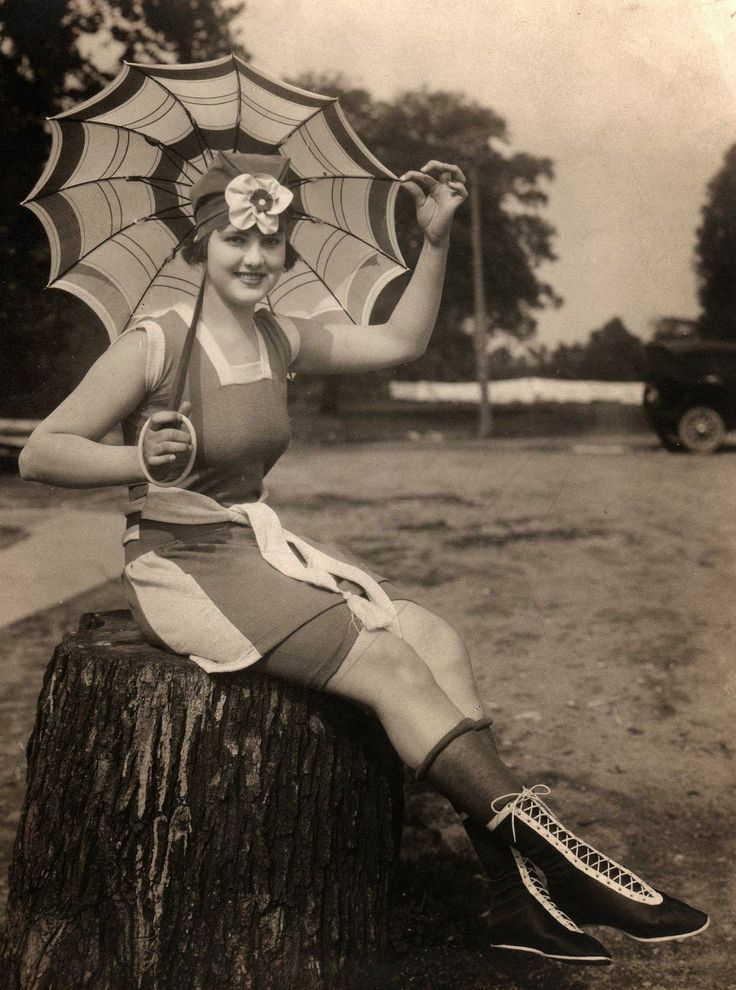 Bathing beauty with umbrella, rolled hose, and hightop shoes. Dayton, Ohio, ca. 1920s