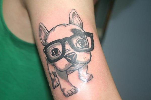 Cute puppy with glasses tattoo on arm