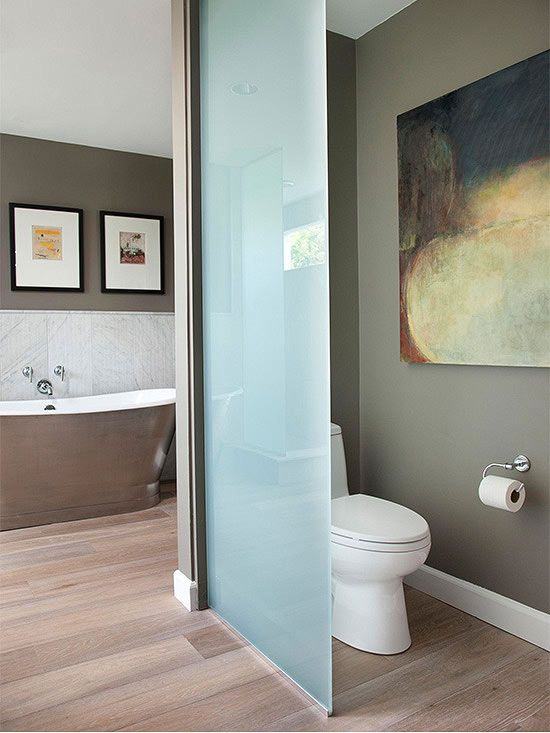 Creating privacy for the toilet using frosted glass takes up far less floor space than a conventional wall.  It also allows light through so the toilet area is less gloomy.