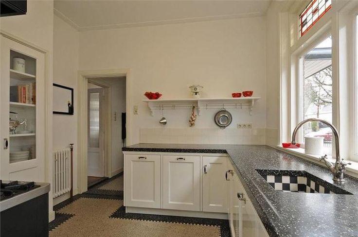 Keuken: plankje, steunen. Geen deur. Zwarte border vloer. Glas in lood bovenlichten. Inbouwkast.