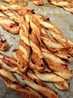 grissini ripieni formaggio e pomodori secchi - 1pasta sfoglia- 100g pomodori secchi sott'olio -100 g emmental -1 tuorlo-parmigiano gratt. pasta sfoglia e spennellata col tuorlo sbattuto. Spolverizzate con del parmigiano.frullate prima i pomodori sgocciolati, poi unite l'emmental e frullate.Stendete su metà sfoglia il composto Richiudete la sfoglia,fare strisce di circa 2 cm. formate i grissini, adagiateli su una placca con carta forno. Spennellate leggermente con il tuorlo rimasto.180° 10–15…