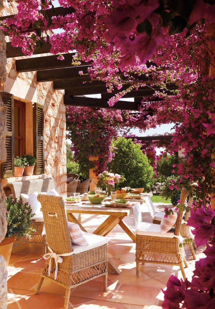 """Un patio en rosa  """"Cuando venimos, en verano, la buganvilla ya ha florecido y lo tiñe todo de rosa"""", explica Amador. Mesa de teca envejecida, en Terraza Balear. Sillas y banco de Rivièra Maison. Cojines a rayas deSleeping Company. El mueble"""