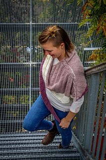 This three-color shawl is made with roughly 880 yards of sport weight yarn and size US 4 needles. In order to make your own, you'll need roughly 440 yards of your main color yarn as well as 220 yards of each of your side colors, which are added with short rows.