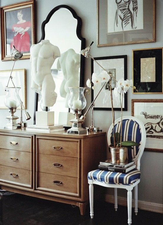 An unusual traditional space with a gallery wall and interesting sculptures beautiful dresser and chair combination ryan korban via decorati