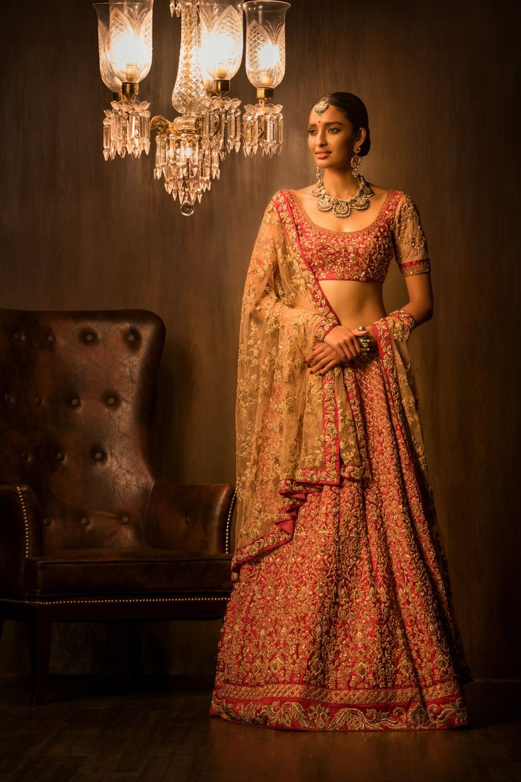 Inspired by the royal courts, the stunning ribbon red lehenga flaunts impeccable antique gold zardosi embroidery. The vintage florals of the Mughal gardens are put in intricate jaals, done in kasab all over. Teamed with a heavily embellished matching cholee, and a dusty pink tulle dupatta with a red zardosi border, making it a perfect regal wedding lehenga. #bridal #trends #bridal2017 #bridalfashion #bridaldress #weddinglehenga