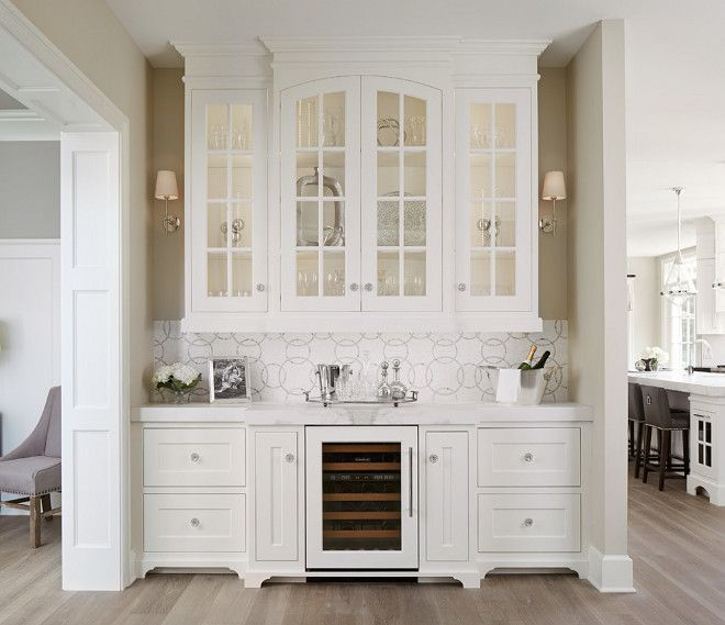 butler's pantry with sconces, hanging cabinets, wine fridge, marble tile splash back