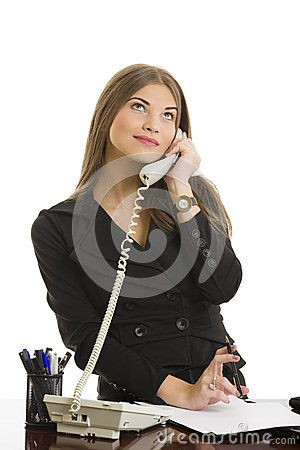 Portrait of pretty business woman looking up and  having happy conversation on phone while playing with pen at office.