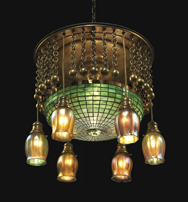 TIFFANY STUDIOS A Geometric Leaded Glass and Bronze Chandelier, circa 1910 with six favrile glass tulip shades 19¼ in. (49 cm.) drop, 16¼ in. (41.2 cm.) diameter of shade shade stamped TIFFANY STUDIOS NEW YORK; favrile glass shades engraved L.C.T.