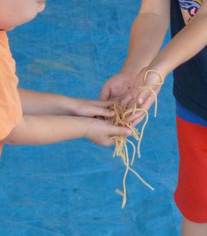spaghetti relay: The kiddos line up across the tarp. One full bowl of noodles (cooked and drizzled with olive oil) at one end, and an empty bowl at the other; pass the spaghetti hands to hands down the line to fill the empty bowl. Use a timer and cheer them on to work speedily.