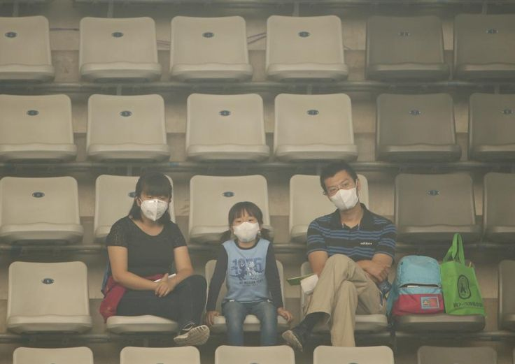 Spectators wearing masks watches the men's singles match between Tomas Berdych of Czech Republic and Pablo Cuevas of Uruguay on a polluted day at the China Open tennis tournament in Beijing, October 7, 2015. REUTERS/Kim Kyung-Hoon