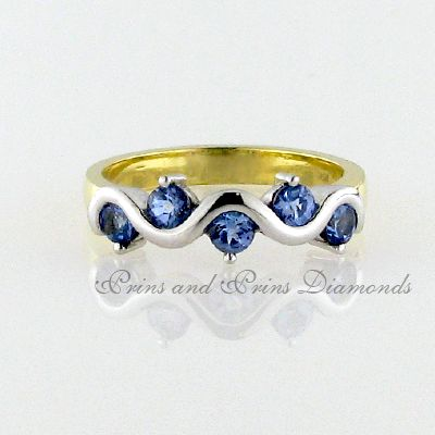 There are 5 = 0.74ct round cut tanzanite's half tube and claw set in an 18k yellow and white gold two-tone band