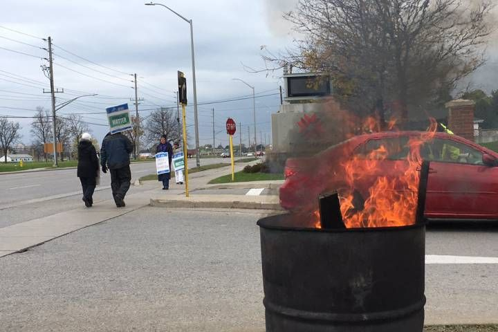 A barrel burns as striking faculty walk the picket lines at Fanshawe College's front entrance on Nov. 1/2017.