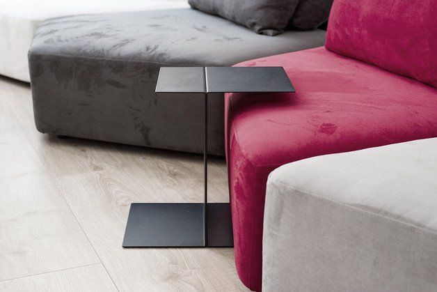 **TWIN** is a couch or coffee table made from sheet metal and powder coated in black.   Its shape makes it possible to push it ''in'' the couch, to bring the table surface closer to you. It is...