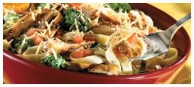 Chicken Brócoli Fettuccine Alfredo: Pechuga de pollo servida en una cama de fettuccine con una cremosa salsa alfredo, cubitos de tomate y brócolis frescos, cubierta de un mix de queso italiano y parmesano. Todo esto Acompañado de pan de ajo. Foto referencial.