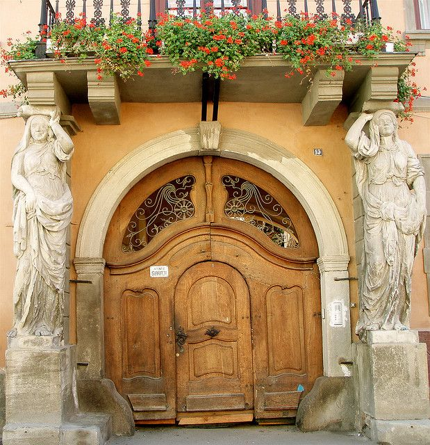 arched wooden door in Sibiu, Romania ... flanked by statues of women ... flowerbox balcony above