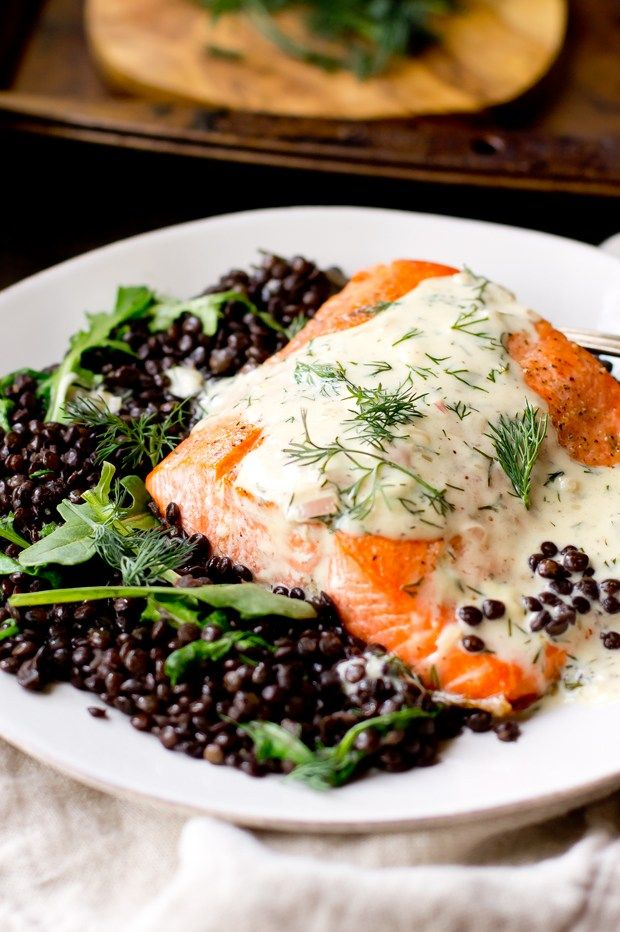 """Elegant salmon with creamy dill sauce served over a bed of the """"caviar"""" of lentils- beluga lentils with wilted arugula."""