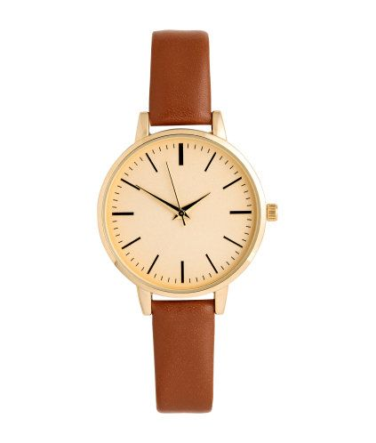 Tawny brown. Metal watch with a narrow, adjustable strap in imitation leather with a metal buckle. Width of strap 1/2 in., overall length 8 1/2 in. Diameter