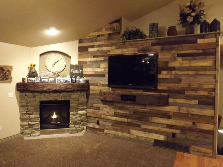 Pallet wood wall and stone fireplace surround with a rustic beam mantel and beam under tv for