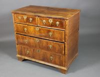 """Lot No 936 A Queen Anne walnut chest with quarter veneered and crossbanded top, fitted 2 short and 3 long drawers with brass escutcheons and drop handles, raised on bracket feet 37""""h x 40""""w x 22""""d (cut), sold for £640"""