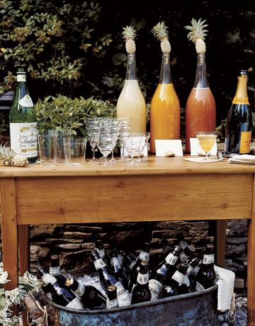 In lieu of a full bar, which can be expensive, Lynn limited the choices to two varieties of beer, and Champagne from which guests could make flavorful Bellinis. She offered three flavors of juice to make Belllinis-- mango, peach, framboise--each labeled, so guests could mix their own. To keep the juices fresh, Lynn stoppered each jug with a mini pineapple. Lynn's thoughtful attention to detail extended even to the calligraphed cards for the table, which incorporated an ink color that…