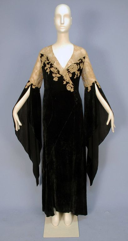 VELVET and LACE DESHABILLE, with WIZARD SLEEVES, 1930's. Black bias cut silk panne velvet wrap with off center self button and loop closure, having sheer ecru Alencon lace bodice top and applique to velvet, curved skirt gores, lace topped long, pointed sleeve open from above the elbow, inside tie at waist. B-42, L-60. (1/2 inch hole near hem, few very tiny holes in lace) very good. $660.