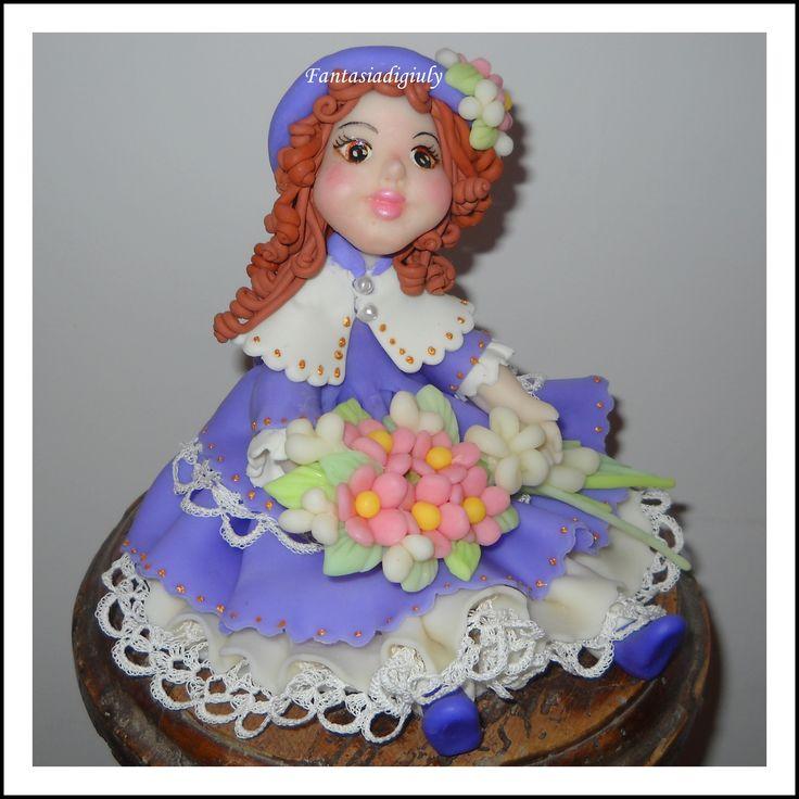 Una creazione di Giuliana B. bambolina seduta in pasta di mais modellata e dipinta a mano. www.fantasiadigiuly.com