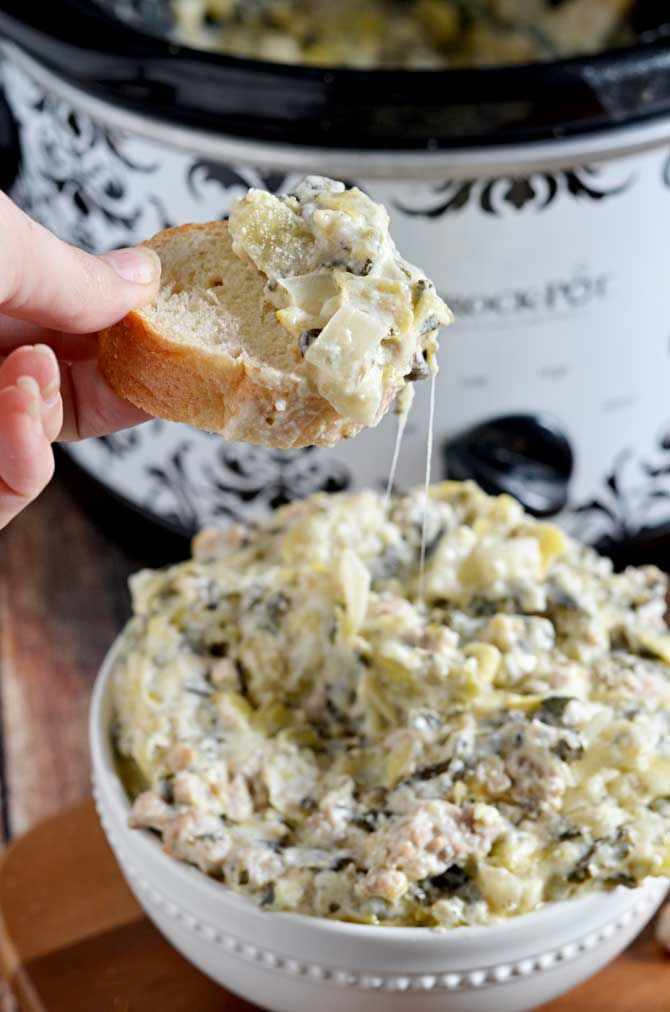 Slow Cooker Sausage, Spinach, and Artichoke Dip. This super cheesy crock pot dip is going to be your new favorite appetizer for parties, tailgates, and more. Best of all, it's so simple to whip together!   hostthetoast.com