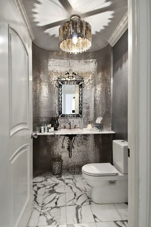 Bathroom with marble tiles floor, gray walls paint color, gray ceiling, Venetian mirror, marble floating bathroom vanity,stainless steel tiles backsplash and Worlds Away Faceted Chandelier.