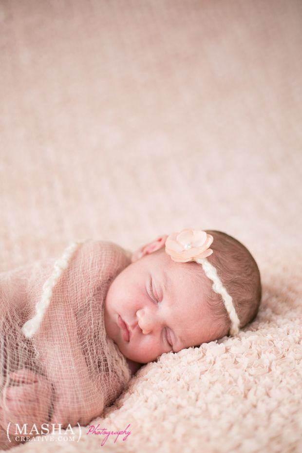 The baby was gently wrapped in a matching peachy mauve cheesecloth wrap this photo is very soft and elegant photographed by nj photographer