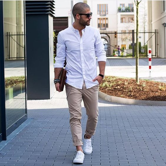 This combination of a white long sleeve shirt and beige chinos is perfect for off-duty occasions. Throw in a pair of white low top sneakers for a more relaxed aesthetic.   Shop this look on Lookastic: https://lookastic.com/men/looks/long-sleeve-shirt-chinos-low-top-sneakers/17929   — White Long Sleeve Shirt  — Dark Brown Leather Zip Pouch  — Beige Chinos  — White Low Top Sneakers  — Black Sunglasses