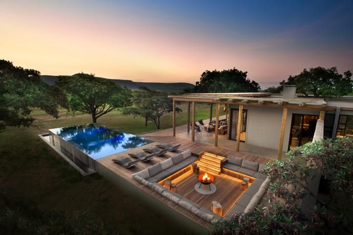The swimming pool is filled from aborehole that supplies the entire property. Astep-down chill area, softly lit by striplights from Streamlight, was designed by Nicholas Plewman Architects. At its centre is a fire bowl from Amatuli. Next to the pool are iroko wood loungers by Meyer von Wielligh for GDFDesign Lab.
