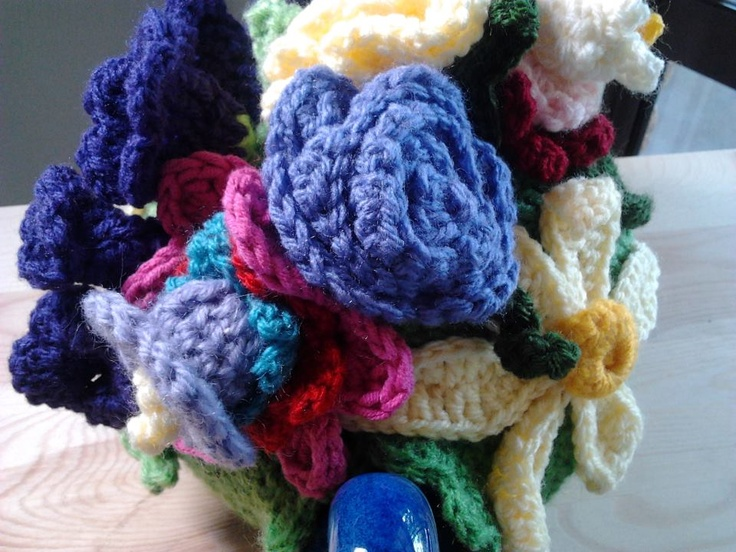 My latest crochet flower tea cosy.  It has a green background and various colours for the floral decorations including a yellow sunflower.