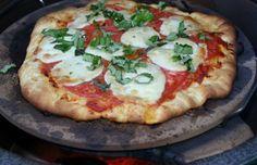 Grilled Pizza Margherita on the Big Green Egg. Pizza Dough - Olive Oil - 2 cloves garlic - grated parmigiano reggiano cheese - ripe tomatoes, sliced - 1 large ball bufalo mozzarella - fresh basil, ct in chiffonade - cornmeal.
