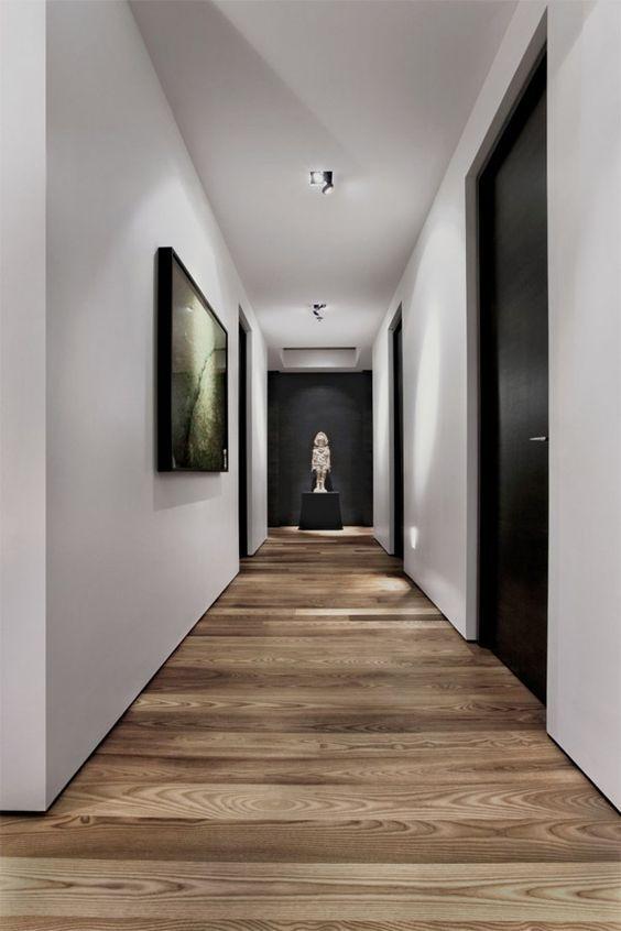 Peinture du couloir : contraste visuel très puissant avec le mur blanc et les portes noires