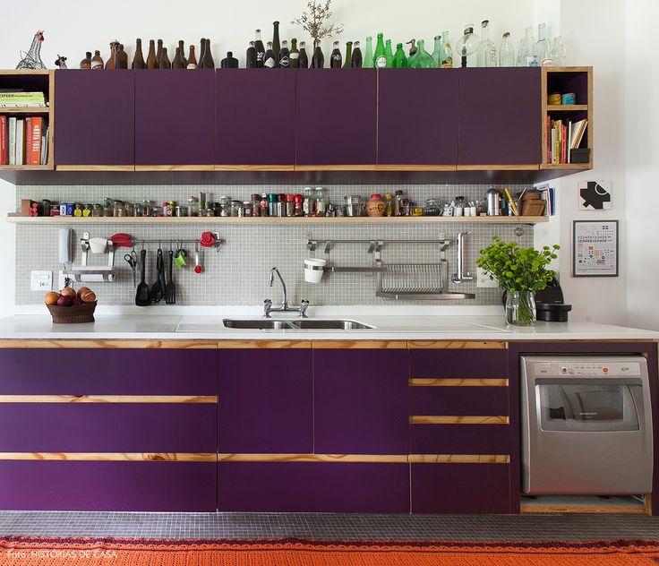 Cozinha ampla tem parede de  pastilhas e marcenaria revestida com fórmica roxa.