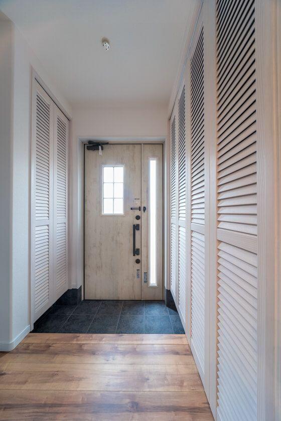 玄関収納の扉は、ウッドワンの「ピノアースシリーズ」ルーバータイプ。玄関ドアはジエスタのC19型/エクリュアイボリー(親子ドアタイプ)です。