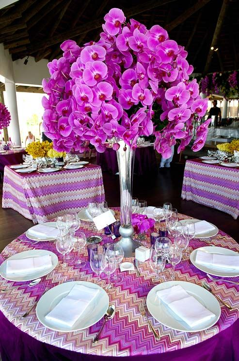 Hot pink orchids overflow in a tall vase atop a chevron-patterned tablecloth.