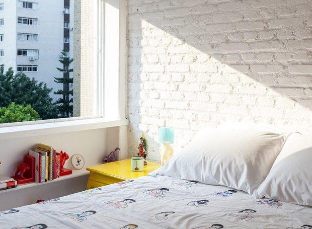 """Tijolo aparente -""""Sem o reboco, a parede da cabeceira deste quarto tem tijolos à vista pintados de branco. O apartamento é projeto do arquiteto Felipe Hass. O espaço abaixo da janela recebeu prateleira e o criado-mudo é do Estúdio Glória."""" No site Casa&Jardim"""